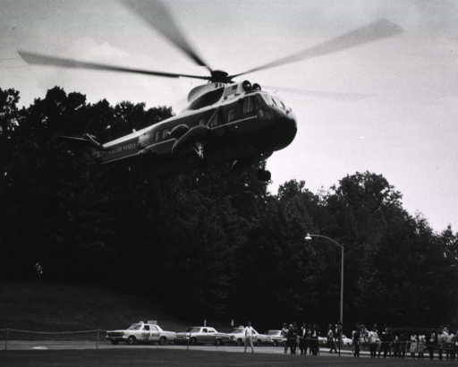 <p>Lyndon B. Johnson, not visible in the photo, is arriving at the &quot;circle&quot; in front of the NIH Clinical Center in the Marine One.  A group of people are standing behind a rope and appear to be experiencing the wake of the helicopter.  Taxis are lined up along the tree-side of the road.  A man with white gloves is standing on the hill in front of the trees.</p>