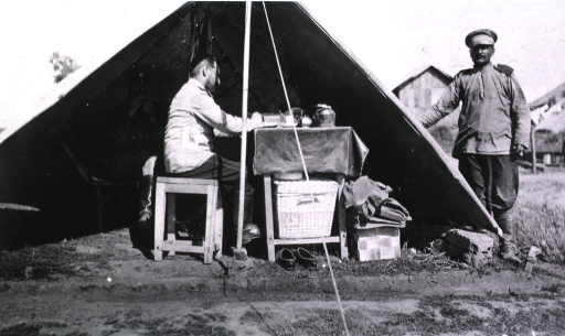 <p>A view of a surgeon sitting at a table writing.  Two other men are in the picture, one sitting inside the tent, the other standing outside beside the tent.</p>
