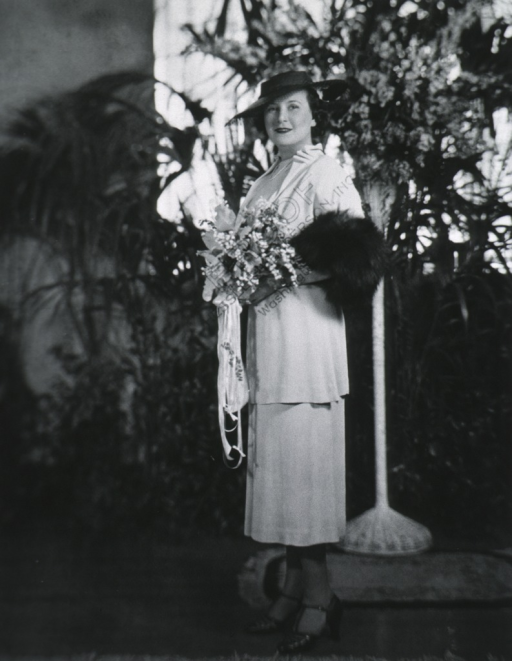 <p>Full length, standing, left pose, full face; wearing wedding outfit with hat; holding bouquet.</p>