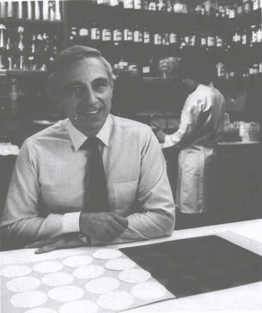 <p>Man with elbows on counter, woman in background.</p>