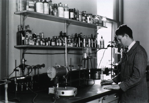<p>Half-length, standing in laboratory, left profile; showing lab equipment and shelves of glass bottles.</p>