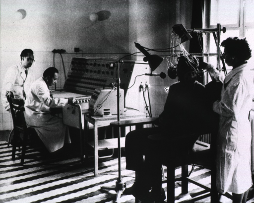 <p>A man sitting in a chair has many wires about his head, a microphone and a light placed in front of his face, and earphones at the sides of his head; a woman attaches electrodes; two men are sitting at a device on the left with many knobs and buttons.</p>