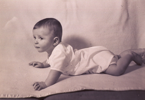 <p>An infant is lying on a blanket; left profile with head raised.</p>