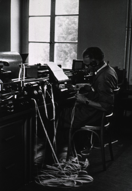 <p>A man is sitting at a desk covered with equipment for monitoring and transmitting epidemiological bulletins.</p>