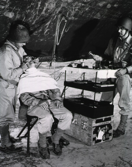 <p>A male patient leans back in a chair and opens his mouth.  A military dentist examines his teeth.  An assistant in uniform holds a pair of scissors.</p>