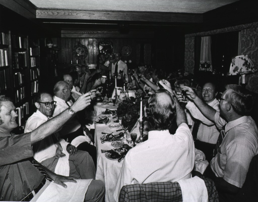 <p>A group of mostly men are seated at two tables raising their glasses at the Bethesda home of Dr. Donald S. Fredrickson.  Standing at the head of the table are Dr. Robert W. Berliner and Mrs. Henriette Fredrickson with arms intertwined holding drinking glasses. On the table are plates of food, candles, and center pieces. There is a book case and a chest on one wall of the room.  Opposite this wall is a large window sill with pictures and a serving dish. Perpendicular to this wall is a mantel holding knick-knacks.  Hanging on the wall above the mantel are decorative plates and a mirror.</p>