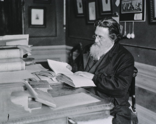 <p>Seated at his desk, left pose, reading.</p>