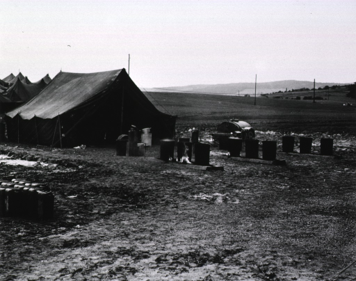 <p>Several barrels sit on fires next to a tent.  In the background are a flat field and hills.</p>