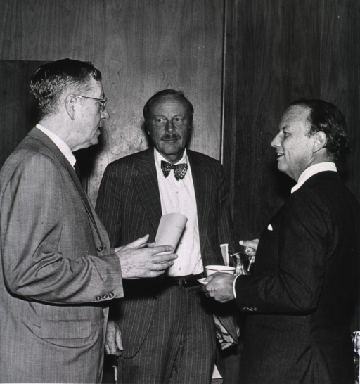 <p>Standing together are  Drs. Thomas Chalmers, Clinical Center director, and Donald S. Fredrickson listening to James A. Shannon.  Dr. Fredrickson is holding a cup and pitcher.</p>