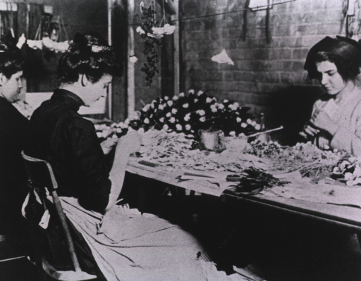 <p>Three women sit at a table and work. Investigations in the garment making industry revealed unsanitary conditions and an excessive rate of tuberculosis.</p>