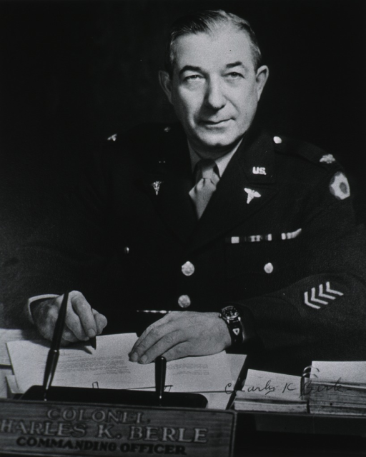 <p>Seated at table, full face, hands on table, wearing uniform.</p>
