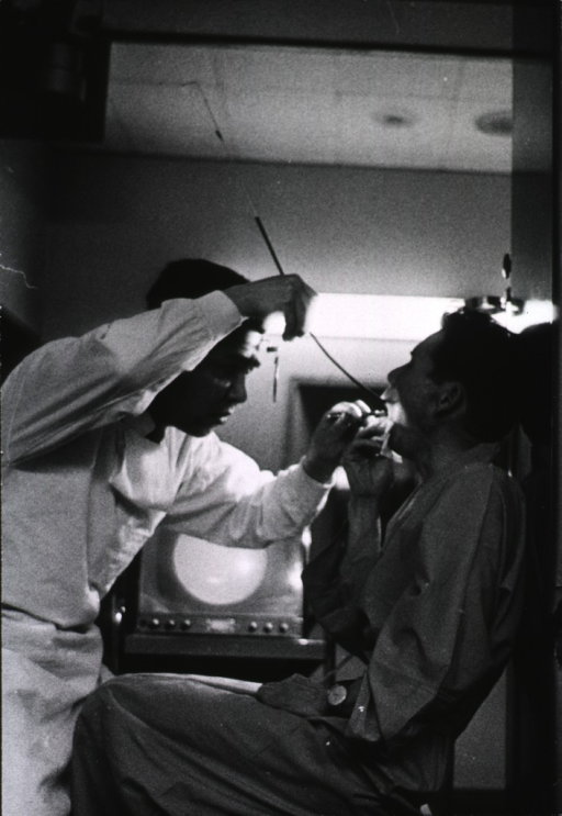 <p>Interior view of an examination room: a physician is examining a patient's lungs using a combination of techniques such as x-rays, television, and fluoroscopy.</p>