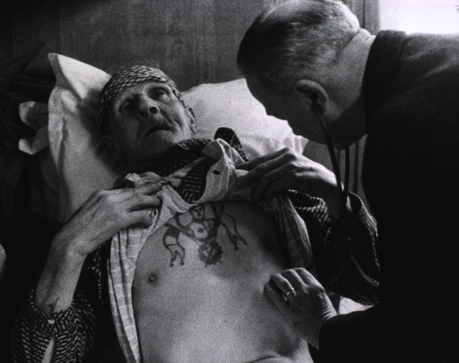 <p>A physician, using a stethoscope, is listening to the lungs of a man who has pulled up his shirt revealing a tattoo on his chest.</p>