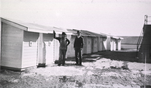 <p>Two men stand beside a row of new outhouses.</p>