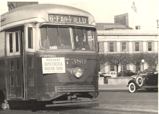 <p>Exterior view:  a streetcar with a &quot;Prevent Diphtheria, Booster Toxoid&quot; sign posted near the front entrance.</p>