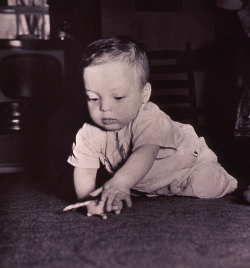<p>An infant is playing on the floor.</p>