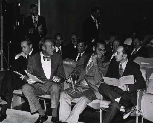 <p>Robert S. Stone, director of the National Institutes of Health (NIH), Thomas C.Chalmers, associate director of NIH, Vernon Knight, Sheldon Wolff, Robert W. Berliner, deputy director (for science) of NIH, and John R. Seal are in the Masur auditorium.  There are &quot;reserved&quot; covers on some of the chair backs. One man is holding what appears to be a &quot;Twentieth Anniversary&quot; program.  Dr. Eugene Braunwald has a pipe in his mouth.  Dr. Fredrickson, director of intramural research, is standing  looking down.  There is an edge of a free-standing black board to the side of the seated people.</p>
