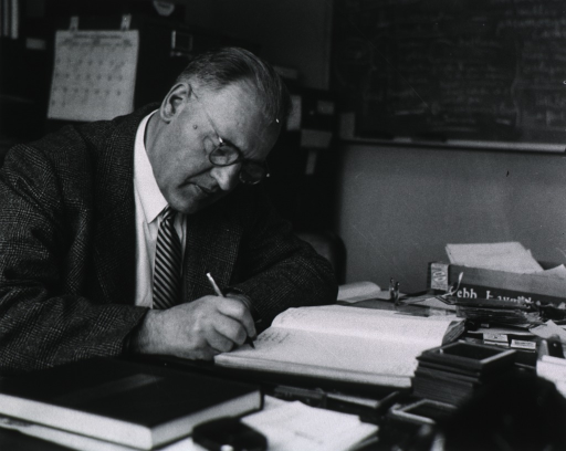 <p>Half-length, right pose, seated at desk; writing in notebook.</p>