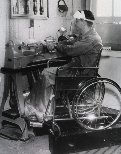 <p>A man sits in a wheelchair and uses a machine to do woodwork.</p>