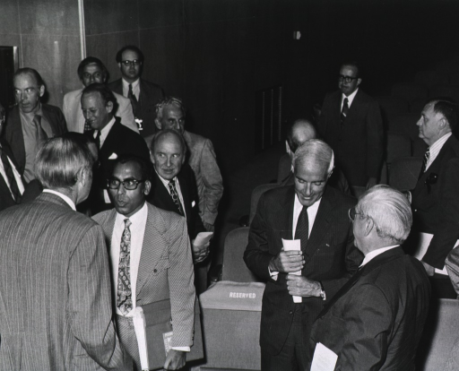 <p>Dr. Charles C. Edwards, assistant secretary for health at the Dept. of Health, Education, and Welfare (DHEW), standing in a group of 13 men at the Masur Auditorium.  Dr. Roy Hertz, of the National Cancer Institute (NCI), is speaking with Dr.  Edwards.</p>