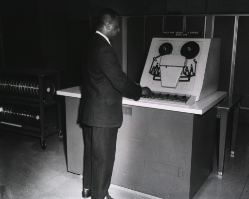 <p>OCCS Computer Room.  John Smith is standing in front of the Bibliographic Service Division's computer for the primary input for MEDLARS.</p>