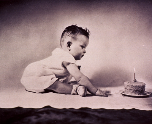 <p>An infant, sitting on a blanket, is leaning towards a cake with a lit candle on it.</p>