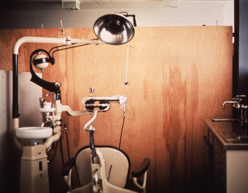 <p>Interior view: dental unit and chair in a partitioned office.  Coat hooks are attached to the partition, a sink is in the lower right corner.</p>