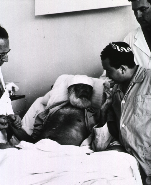 <p>An old man is lying in a hospital bed; he is speaking to a young man on the right as a physician is taking his pulse on the left.</p>