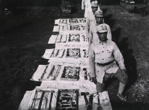 <p>Exterior view: tools are in rows on white material lying on the ground; soldiers are on one knee beside the tools.</p>
