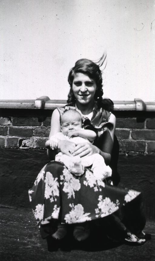 <p>A mother sits with her infant on the roof of a building.</p>