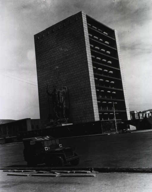 <p>An army jeep is parked in front of a nine-story building.  Next to the building, on a bas relief pedestal, stands a three-story high sculpture of an unidentified classical warrior standing on a reclining beast.</p>
