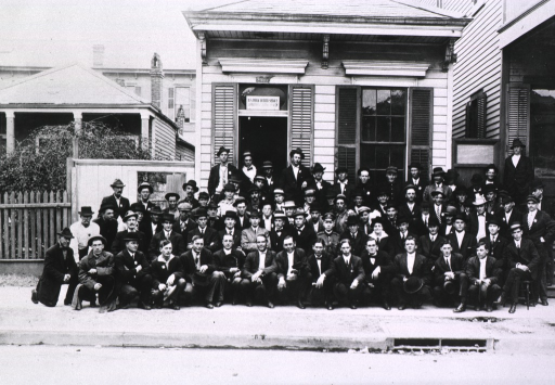 <p>Group portrait of U.S. Public Health Service workers posing in front of sanitary district no. 7 headquarters during the New Orleans plague campaign.  African American(s) in group.</p>