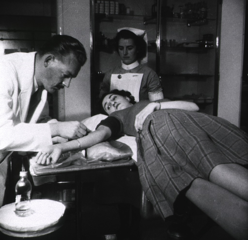 <p>Blood being removed from donor's arm for transfusion.</p>