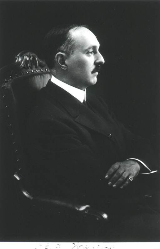 <p>Half length, seated in chair, right profile, arms crossed.</p>