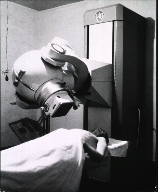 <p>Interior view: showing a man lying on a bench beneath a large piece of medical equipment.</p>
