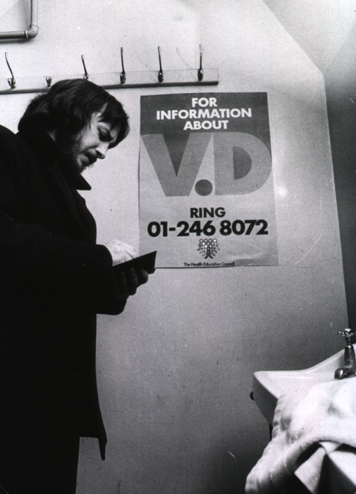 <p>A man is writing down a phone number from a poster about venereal disease that is hanging on the wall in a public bathroom.</p>