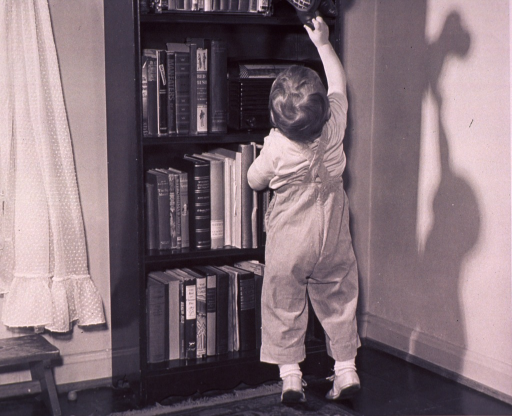 <p>A child is reaching for a toy on a bookshelf.</p>