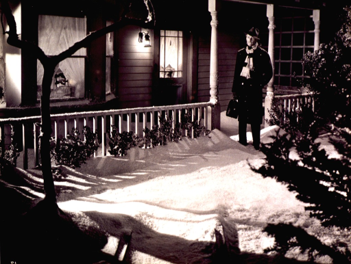 <p>A man in a coat and hat stands on the snow-covered steps of a front porch on the set of a movie.  A small child peers through the curtains of the front door.</p>