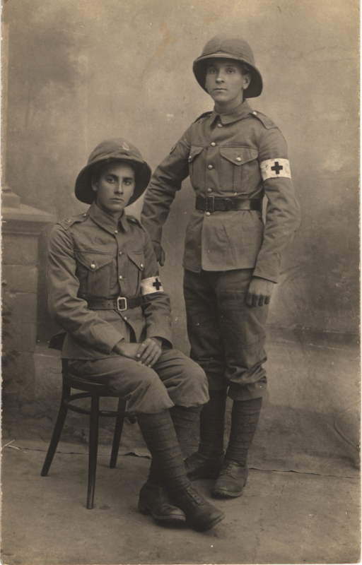 <p>Postcard featuring a black and white photograph of two male Red Cross members dressed in military uniforms. Both men have Red Cross symbols on their armbands. One of the men is sitting in a chair and the other is standing next to him holding the edge of the chair with his right hand.</p>