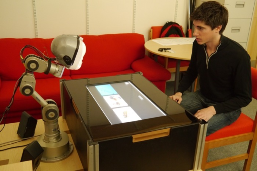 Overview of the experimental set-up, showing the LightHead robot, the touchscreen used to play an interactive learning game and the participant.The individual in this image has given written informed consent (as outlined in PLOS consent form) to publish these case details.