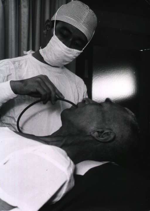 <p>A physician is pushing a tube down the throat of a patient.</p>