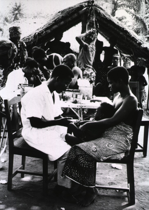 <p>A young man is taking a blood sample from a young child who is sitting on her mother's lap; in the background other health workers are sitting at a table, beyond them is a small hut; there are several women and children present.</p>