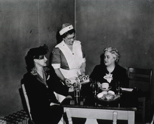 <p>Two women sit at a table.  There is a plate of donuts on the table.  One of the women holds a cup of coffee.  A Red Cross volunteer stands and serves tea to the women.</p>
