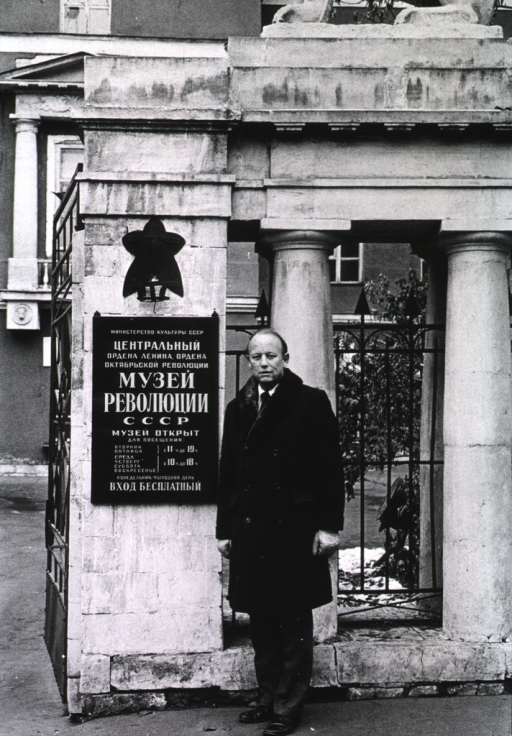 <p>Dr. Donald S. Fredrickson, of the National Heart, Lung, and Blood Institute (NHLBI), is standing at a gateway by the sign for the Revolutionary Museum in Moscow. The entry way is open leading to a multi-story building.  Behind Dr. Fredrickson are columns in front of a speared iron fence.</p>