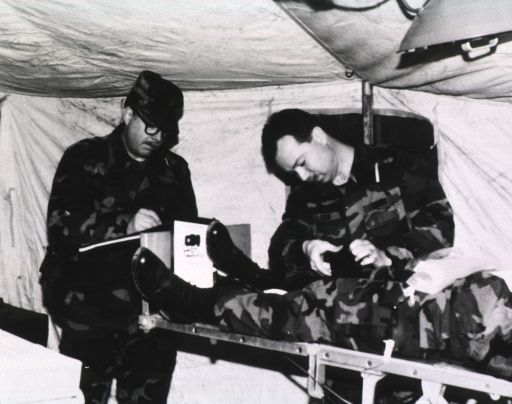 <p>Two medical attendants treat a patient on a stretcher in a tent; all are wearing uniforms.</p>