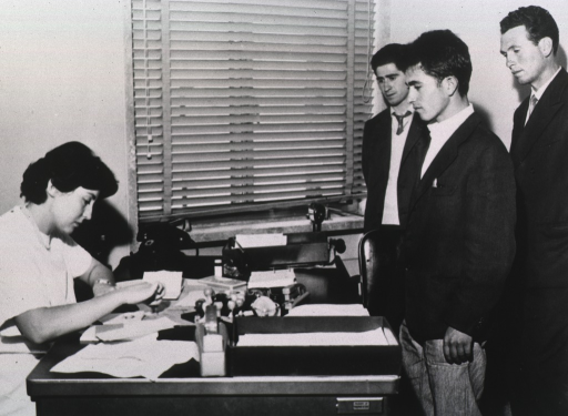 <p>Three men in suits stand before a desk at which sits a female medical professional.</p>