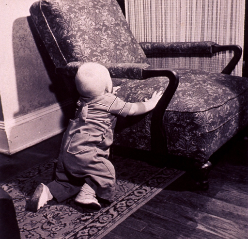 <p>An infant is attempting to stand up with the aid of a chair.</p>