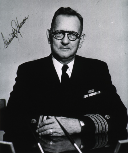 <p>Head and shoulders, seated at desk, full face; wearing glasses and naval uniform(Captain); arms resting on desk.</p>