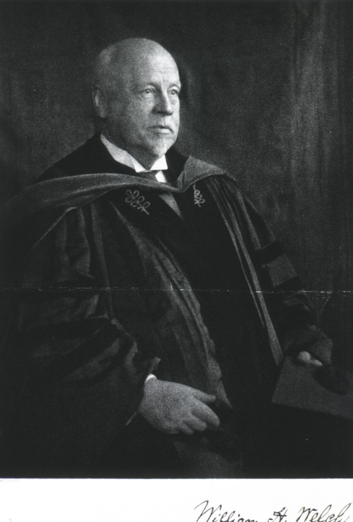 <p>Half length, seated, body to right, wearing academic robe and holding cap.</p>