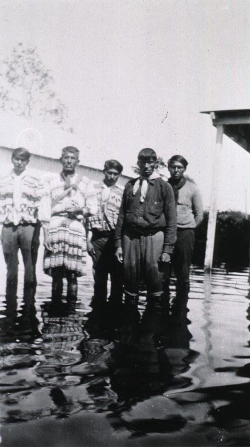<p>Showing a group of Seminole Indians standing in the flood waters after a severe hurricane.</p>